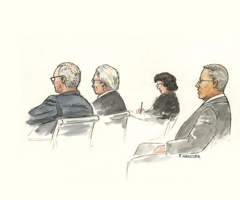 Angeklagter sitzend mit Anwälten.