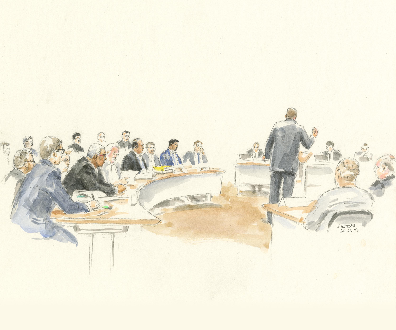 Die 14 Angeklagten sitzend und ein Verteidiger stehend.