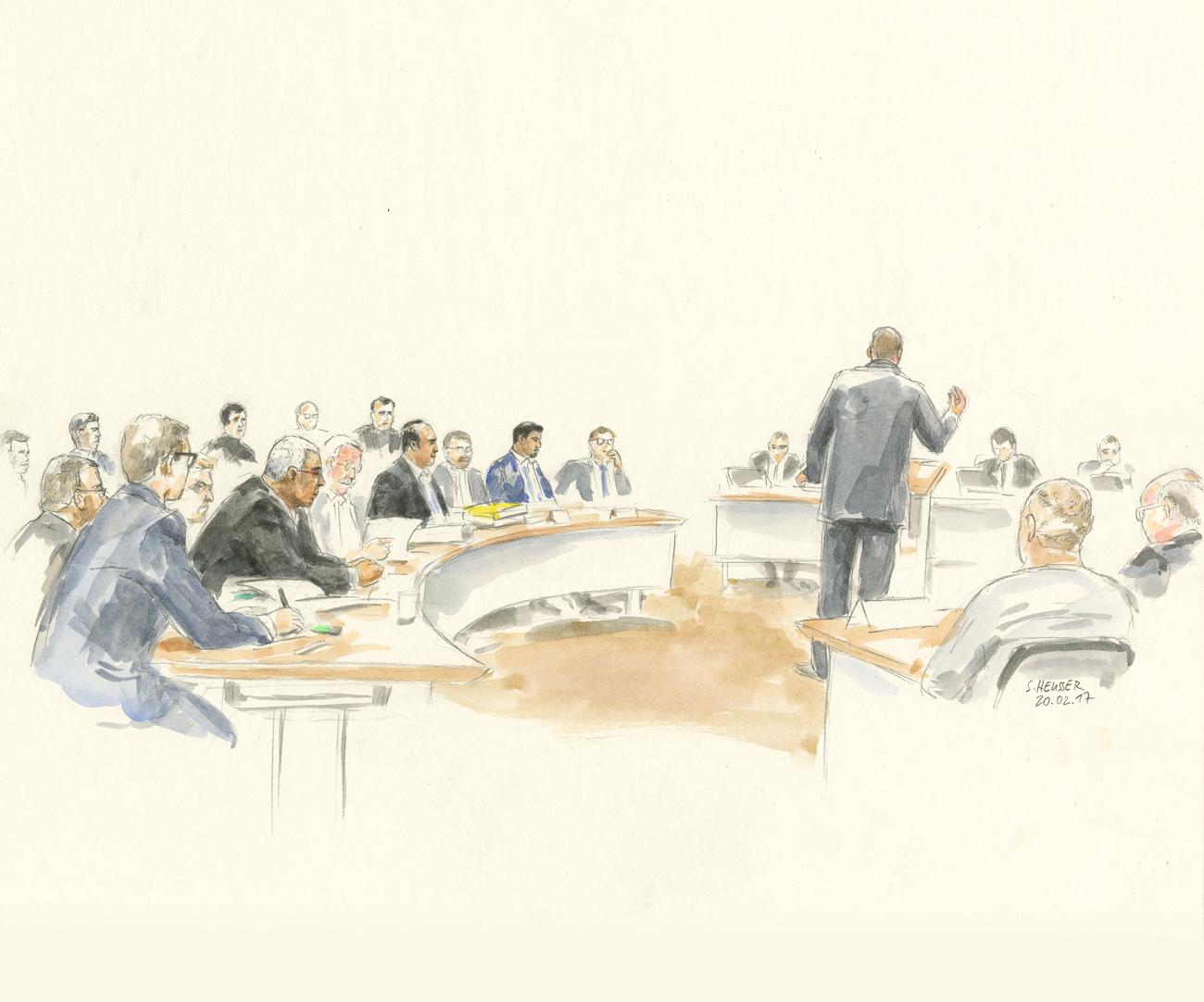 Die 14 Angeklagten sitzend und ein Verteidiger stehend